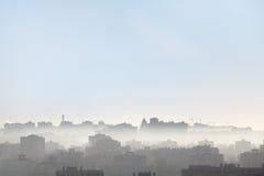 Vroege ochtend over de daken van stad, silhouetten van gebouwen Royalty-vrije Stock Afbeeldingen