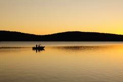 Vroege ochtend vissersboot op een meer bij dageraad Royalty-vrije Stock Foto's