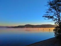 Vroege ochtendmist die van Loch Lomond Schotland toenemen stock fotografie