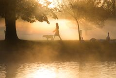 Vroege ochtendmist en mist over meer met langs passers Royalty-vrije Stock Foto