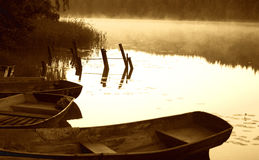 Vroege ochtendschets door het mistige meer met boten stock afbeelding