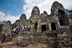 Vroege ochtendtoerist die de Bayon-tempel, een deel bezoeken van de ruïne oude tempel Kambodja van Angkor Thom Stock Afbeelding