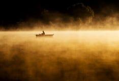Vroege ochtendzonsopgang, roeien op het meer in een reusachtige mist Royalty-vrije Stock Afbeelding