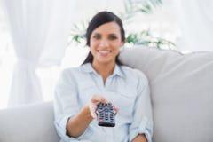 Vrolijk aantrekkelijk brunette die TV-kanalen veranderen Stock Foto's