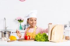 vrolijk Afrikaans Amerikaans jong geitje in schort en chef-kokhoed het koken royalty-vrije stock foto's