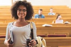 Vrolijk Afrikaans meisje in auditieve ruimte bij universiteit royalty-vrije stock afbeelding