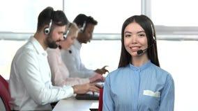 Vrolijk Aziatisch bureaumeisje met medewerkersachtergrond stock footage