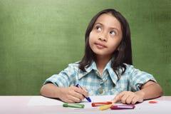 Vrolijk Aziatisch kind die iets veronderstellen aan tekening met kleurpotlood Stock Foto
