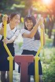 Vrolijk Aziatisch tiener twee toothy het glimlachen gezicht in openbare speelplaats stock fotografie