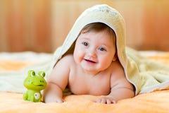 Vrolijk babykind onder een handdoek met een kap daarna stock foto