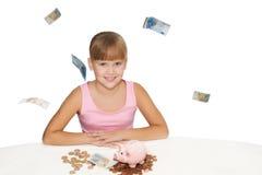 Vrolijk babymeisje met vliegend geld en geïsoleerd spaarvarken Stock Afbeelding