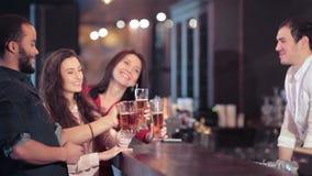Vrolijk bedrijf van meisjes en een kerel bij de bar stock footage
