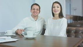 Vrolijk bedrijfspaar die aan de camerazitting spreken in een koffie stock video