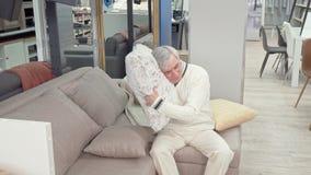 Vrolijk bejaarde die zachte kussens op verkoop proberen bij meubilairopslag stock videobeelden