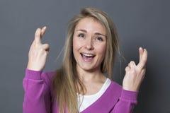 Vrolijk blond meisje het vertrouwen op geloof in vast de kruising van haar vingers Stock Afbeeldingen