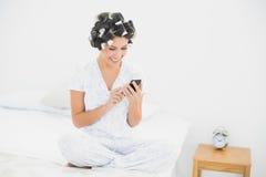 Vrolijk brunette in haarrollen die een tekst op bed verzenden Stock Afbeelding