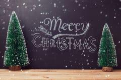 Vrolijk de kaartontwerp van de Kerstmisgroet met bord het van letters voorzien en Kerstbomen op houten lijst Royalty-vrije Stock Foto