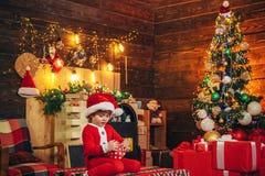 Vrolijk de stemmingsspel van het jongens leuk kind dichtbij Kerstmisboom Ge?soleerd op witte achtergrond Vrolijke en heldere Kers stock afbeelding