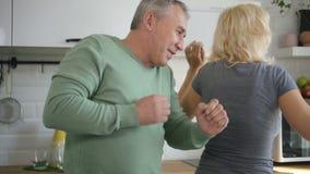 Vrolijk echtpaar die in modern keukenbinnenland dansen stock footage