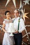 Vrolijk echtpaar die zich dichtbij de bakstenen muur verfraaid w bevinden Stock Foto's
