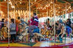 Vrolijk-gaan-rond carrousel met kinderen en volwassenen die pret hebben stock afbeeldingen