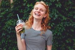 Vrolijk gembermeisje met in hand cocktail, gestemde foto stock fotografie