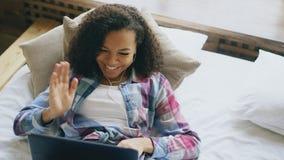 Vrolijk gemengd rasmeisje die videopraatje met vrienden hebben die laptop camera met behulp van terwijl het liggen op bed Stock Fotografie