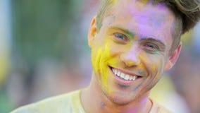 Vrolijk gezicht van de jonge knappe mens die gekleurd poeder in lucht werpen bij festival stock video
