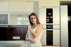 Vrolijk glimlachend jong wit huidwijfje met het lange donkerbruine haar stellen op de keuken royalty-vrije stock foto's