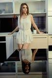 Vrolijk glimlachend jong wit huidwijfje met het lange donkerbruine haar stellen op de keuken royalty-vrije stock afbeeldingen