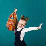 Vrolijk glimlachend meisje met het grote rugzak springen en havin stock foto's