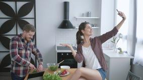 Vrolijk grappig jongen en meisje die selfie foto op mobiele telefoon en grimas nemen terwijl het koken van gezonde plantaardige s stock footage