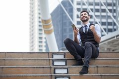 Vrolijk het Bedrijfsmens Vieren Succes met mobiele telefoonzitting op de treden in stedelijke stad die in openlucht, goed nieuws  royalty-vrije stock afbeeldingen