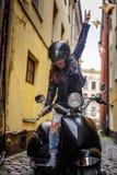 Vrolijk hipstermeisje die een leerjasje en gescheurde jeans dragen die zich in een zwarte klassieke autoped op de oude engte bevi stock foto