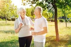 Vrolijk hoger paar die samen na jogging in het park rusten Royalty-vrije Stock Afbeeldingen