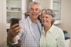 Vrolijk hoger paar die selfie in keuken nemen royalty-vrije stock fotografie