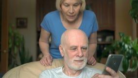 Vrolijk hoger paar thuis Echtgenoot die smartphone, het doorbladeren, het lezen gebruiken Vrouw het kussen stock video