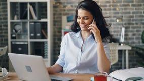Vrolijk jong brunette die op mobiele telefoon babbelen en laptop in bureau met behulp van stock video