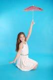 Vrolijk jong meisje in witte kleding met een paraplu Stock Foto's