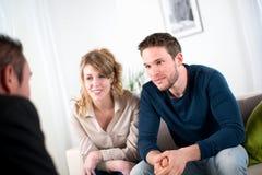 Vrolijk jong paar met verkopersagent thuis Stock Foto