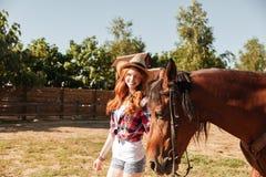 Vrolijk jong vrouwenveedrijfster het lopen verstand haar paard op boerderij Stock Afbeeldingen