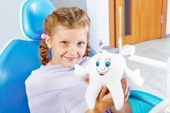 Vrolijk kind dat een stuk speelgoed tand houdt royalty-vrije stock afbeelding