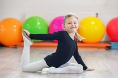 Vrolijk kleutermeisje die gymnastiek in de gymnastiek doen Het concept sporten, onderwijs, hobbys, opleiding en dans stock afbeeldingen
