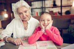 Vrolijk leuk meisje die grappig terwijl het doen van thuiswerk met oma voelen royalty-vrije stock foto's