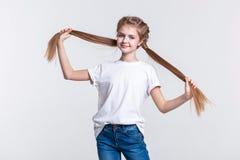 Vrolijk leuk meisje die haar lange staarten uitspreiden en hun lengte tonen stock fotografie