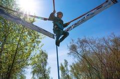 Vrolijk leuk weinig jongen die op een trampoline tegen de blauwe hemel springen Stock Afbeelding