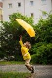 Vrolijk loopt weinig jongen op de werf van het huis met een paraplu in een hand Royalty-vrije Stock Afbeelding