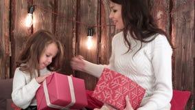 Vrolijk mamma en haar leuke dochter die giften ruilen en elkaar koesteren stock videobeelden