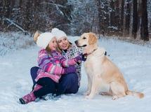 Vrolijk mamma en haar leuke dochter met hun hondgolden retriever in de winter Stock Foto