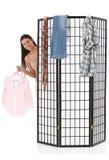 Vrolijk meisje dat zich omhoog achter kledend paneel kleedt Stock Foto's